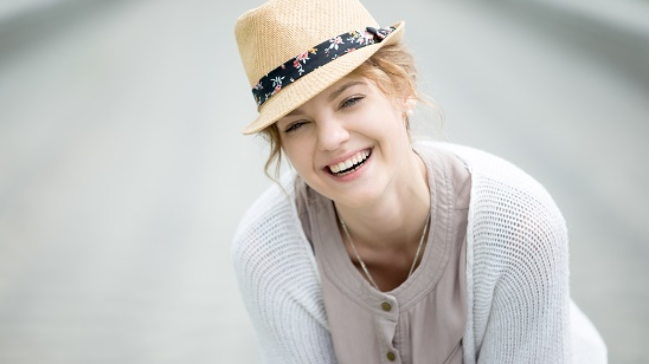 Headshot portrait of laughing beautiful caucasian woman wearing casual clothing. Young female standing on the street in summer and looking at camera. Attractive model posing with cheerful expression