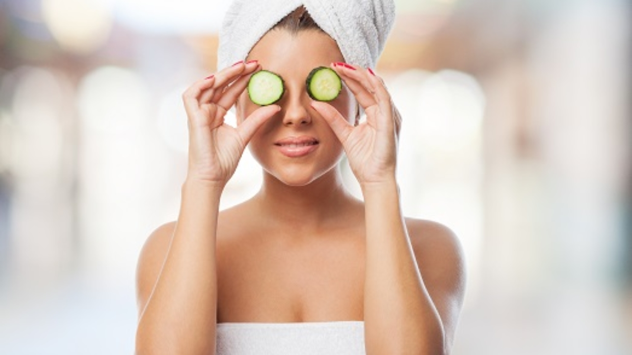 portrait of beautiful young woman putting on cucumbers on her eyes